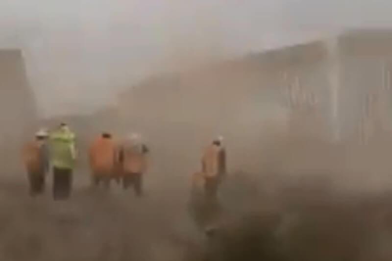 Trabajadores observan la caída de parte del muro fronterizo por los vientos provocados por la entonces Tormenta Tropical Hanna al sur de Texas